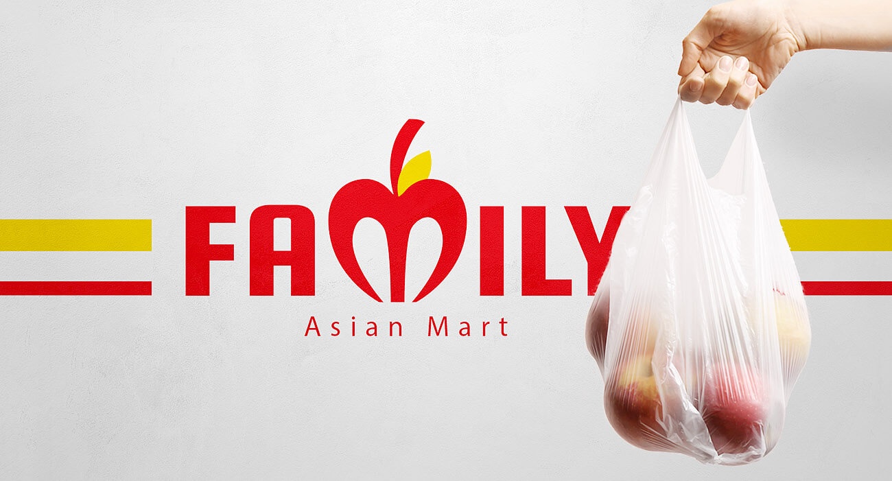 Man holding bag next to Family Asian Mart sign